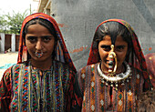 Two young Jat women, one wearing traditional brass Jat tribal nose ring, jewellery and clothing, Bhidara village, Kutch, Gujarat, India, Asia