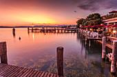 View of golden sunset and restaurant overlooking Lake Garda, Sirmione, Lake Garda, Lombardy, Italian Lakes, Italy, Europe