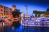 View of Scaliger Castle and boats in harbour at dusk, Sirmione, Lake Garda, Lombardy, Italian Lakes, Italy, Europe