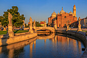 View of statues in Prato della Valle during golden hour and Santa Giustina Basilica visible in background, Padua, Veneto, Italy, Europe