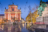 Ornate facade of Franciscan Church of the Annunciation and Preseren Monument in Plaza Presernov at dusk, Ljubljana, Slovenia, Europe