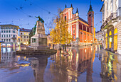 Reflections of the ornate facade of the Franciscan Church of the Annunciation and Preseren Monument in Plaza Presernov at dusk, Ljubljana, Slovenia, Europe