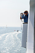 Captain with binoculars on ferry between Vitte and Schaprode, Hiddensee, Ruegen, Baltic Sea coast, Mecklenburg-Vorpommern, Germany