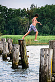 Boy jumps into water in Waase village on Ummanz, Ruegen, Baltic Sea coast, Mecklenburg-Vorpommern, Germany