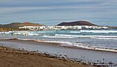 Surfer at the Playa de Famara and the village of La Caleta de Famara, Atlantic Ocean, Lanzarote, Canary Islands, Islas Canarias, Spain, Europe