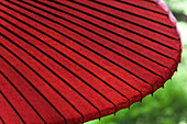 Close-up, detail, of a decorative opened red paper umbrella.