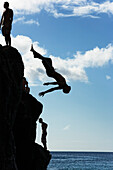Silhouetted young men and a man upside down mid-air, jumping off of the 'da Big Rock' or 'Jump Rock', a rock that is perfectly positioned in the bay at Waimea Bay Beach Park, O'ahu, Hawaii.