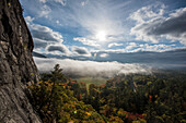 Early morning fog covering the bright fall foliage of New Hampshire as seen from Humphrey's Ledge in North Conway, New Hampshire.