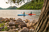 Side view of couple kayaking near shore of Jordan Pond in Acadia National Park, Maine, USA
