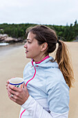 Side view of woman drinking coffee on beach, Acadia National Park, Maine, USA