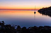 Silhouette of sailboat at sunset moored in Duck Harbor, Isle au Haut, Acadia National Park, Maine, USA