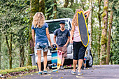 Two women carrying skateboards walking towards male friend waiting and leaning on parked car, Bali, Indonesia