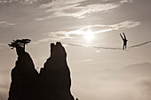 Silhouette of man doing handstand on highline against sun and over foggy hills, Lower Austria, Austria