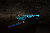 Man paddleboarding and light painting in underground river, Vienna, Austria