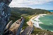 Young woman lying on edge of rock with view from Pico da Coroa Hill to Lagoinha do Leste Beach, Florianopolis, Santa Catarina Island, Brazil
