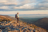 A young woman takes in the view from the top of Mount Abraham, along the Appalachian Trail in Maine's western mountains.