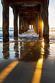 View underneath Manhattan Beach pier at sunset, Los Angeles, California, USA