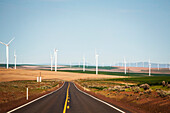 Clear sky over empty countryside highway in front of wind farm, Oregon, USA