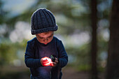 Boy holding and using headlamp in forest at evening, Harrison Hot Springs, British Columbia, Canada