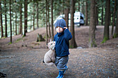 Boy holding teddy bear in forest, Harrison Hot Springs, British Columbia, Canada