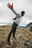 Backpacker throwing body into wind on rocky ridge, Merritt, British Columbia, Canada