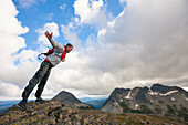 Hiker leaning over supported by strong wind on rocky mountain ridge, Merritt, British Columbia, Canada