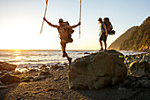 Two backpackers having fun while hiking along beach at sunset, Lost Coast Trail, Kings Range National Conservation Area, California, USA