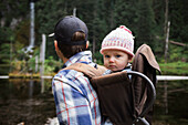 Baby girl sitting in backpack carrier during forest hike, Washington, USA