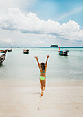 Young woman in bikini walking on beach towards sea with raised arms, Tambon Ko Tarutao, Chang Wat Satun, Thailand