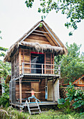 Woman doing yoga on porch of jungle hut, Tambon Ko Tarutao, Chnag Wat Krabi, Thailand