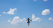Woman in mid-air with bouquet against sky
