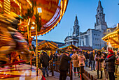 View of carousel and Christmas Market stalls at Christmas Market, Millennium Square, Leeds, Yorkshire, England, United Kingdom, Europe