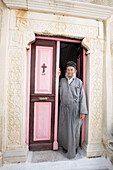 Greek Orthodox priest standing in doorway of Moni Taxiarchon Monastery, Serifos, Cyclades, Aegean Sea, Greek Islands, Greece, Europe