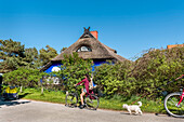 Cyclists in front of Blaue Scheune, Vitte, Hiddensee island, Mecklenburg-Western Pomerania, Germany