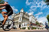 Cyclists in front of Hotel Ahlbecker Hof, Ahlbeck, Usedom island, Mecklenburg-Western Pomerania, Germany