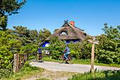 Cyclists in front of Blaue Scheune, Vitte, Hiddensee island, Mecklenburg-Western Pomerania, Germany
