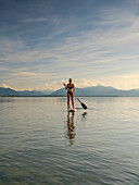 A young woman doing stand-up paddling on the Chiemsee, in the background the Chiemgau Alps, Chieming, Upper Bavaria, Germany