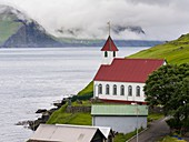 The island of Kunoy with village Kunoy and church. In the background island Kalsoy. Nordoyggjar (Northern Isles) in the Faroe Islands, an archipelago in the north atlantic. Europe, Northern Europe, Scandinavia, Denmark, Faroe Islands.