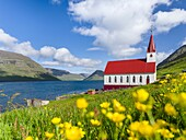 The church in village Husar on Kalsoy, in the background the island of Bordoy and Klaksvik. Nordoyggjar (Northern Isles) in the Faroe Islands, an archipelago in the north atlantic. Europe, Northern Europe, Scandinavia, Denmark, Faroe Islands.