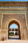 Zellij mosaics and arabesque Moorish plasterwork of the Bab Mansour gate. Named after the architect, El-Mansour, completed in 1732 the design of the gate plays with Almohad patterns. Meknes Morocco.