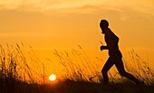 Male jogger at sunrise on a frosty winter morning. Billingham, north east England. United Kingdom.