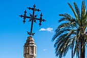 A cross on a stone column next to a palm tree in front of the church, Selva, Mallorca, Spain