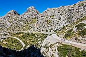 Cyclists on the famous winding road leading to Torrent de Pareis, Sa Calobra, Tramuntana Mountains, Mallorca, Spain