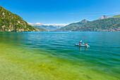 Two guys go canoeing on lake Como, Menaggio, Como province, Lombardy, Italy, Europe