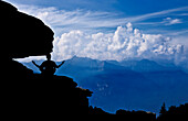 Man practice Zen meditation on the rocks admiring the Lepontine Alps from Brogoldone refuge, Lumino, Canton of Ticino, Switzerland, Europe