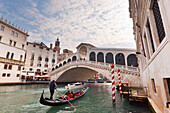 A traditional venetian gondola on Grand Canal, under Rialto Bridge, Venice, Veneto, Italy