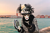 Typical mask of Carnival of Venice at San Giorgio island with San Marco Bell Tower on background, Venice, Veneto, Italy