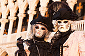 A couple of typical mask of Carnival of Venice with Ducal Palace on background, Venice, Veneto, Italy