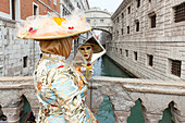Typical mask of Carnival of Venice in front of Bridge of Sighs, Venice, Veneto, Italy