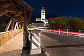 Car transit at night in front the church of Glorenza, Val Venosta, Sudtirol, Italy.